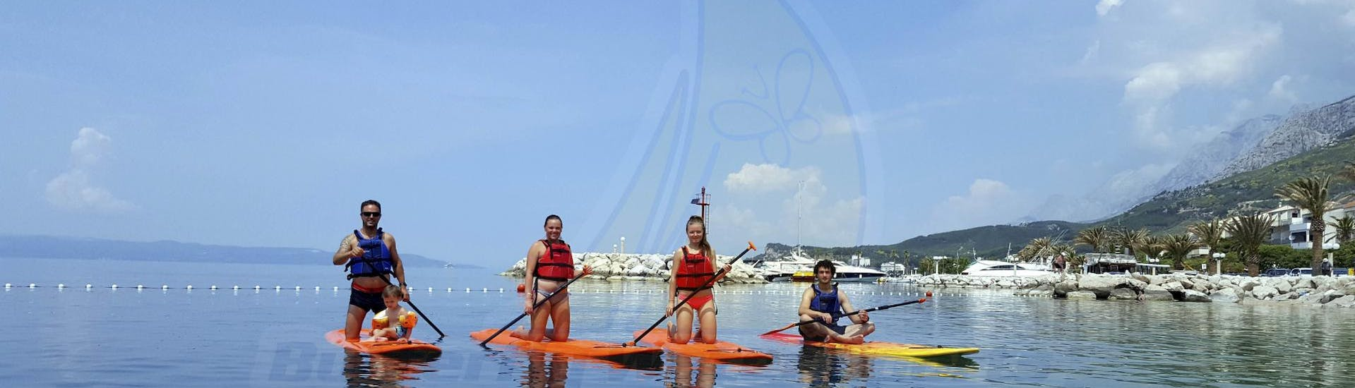 Having purchased SUP Rental - Makarska Riviera offered by Butterfly Diving & Sailing, a family is enjoying a great time paddling on a SUP on the Adriatic Sea.