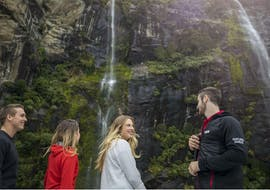 A group of people and their nature guide are marvelling at the dramatic waterfalls during the Milford Sound Nature Day Trip from Queenstown with Southern Discoveries.