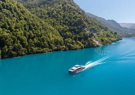A Southern Discoveries catamaran can be seen cruising along Lake Wakatipu as part of the Spirit of Queenstown Cruise.