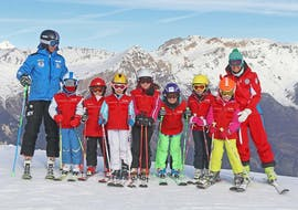 Two ski instructors are smiling at the camera with the young participants of the kids ski lessons (4-14 y.) - All Levels organized by the ski school Scuola di Sci Sauze Sportinia in the ski resort Via Lattea.