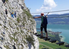 A woman crossing the adventurous suspension bridge of the Via Ferrata for panorama fans on the Drachenwand under the guidance of the experienced guides of Bergführer Salzburg.
