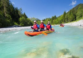Three friends are paddling along the turquoise Lech river during their Canoe-Rafting on the Lech River - Half Day Tour with Fun Rafting Lechtal.