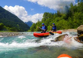 Two participants of the Canoe Rafting on the Lech River - Full Day Tour with BBQ organized by Fun Rafting Lechtal are mastering a rapid on the river in their inflatable canoe.