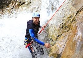 A participant of the Canyoning in the Hochalpschlucht with Fun Rafting Lechtal is roping down a thundering waterfall in the canyon.