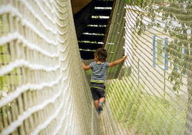 A young child is walking along a net during the Adventure Park - Mini Pitchoun Route with Accroche-toi aux branches.