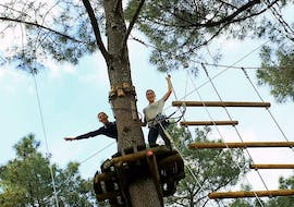 Two girls are on a platform in the trees, ready to start their Adventure Park - Discovery Route with Accroche toi aux branches.