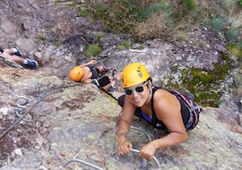 A woman is climbing a cliff during her Via Ferrata activity in Ardèche - Pont du Diable with Les Intraterrestres.