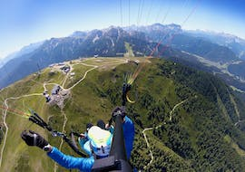 A tandem pilot from Tandemflights Kronplatz and his passenger are enjoying the view of the Puster Valley during the Thermic Tandem Paragliding from Plan de Corones.