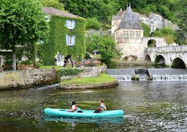 Friends are paddling on the Dronne river in the middle of the charming village of Brantome during their 4km canoeing tour with Allo Canoës Dordogne.