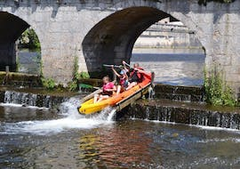 A family is passing a slide on their canoe during their day with Canoe Rental in Brantôme on the Full Day on the Dronne - 12km tour.