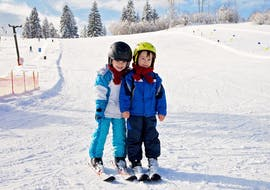 """Two children on skis during their Kids Ski Lessons """"Kids Club"""" (5-13 y.) for Beginners with Heli's Skischule Saalbach-Hinterglemm."""