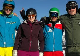 Four adults are holding each other during their adult and teen lessons for beginners with Hedi's Skischule Saalbach-Hinterglemm.