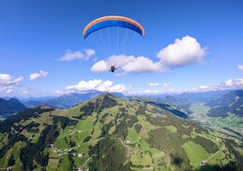A tandem pilot from TirolAir and his passenger can be seen floating high above the mountain peak while paragliding from the Hohe Salve.