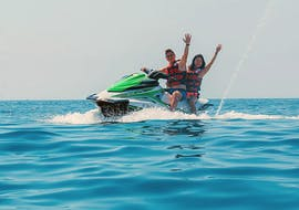 A couple drives fastly with the jet ski in the beautiful sea during the Jet Ski Rental in Salou or Cambrils organized by Estació Nàutica Costa Daurada.