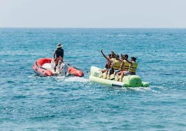 A group of friends let themselves be pulled by the boat through the sea during a Banana Boat Ride in Salou organized by Estació Nàutica Costa Daurada.