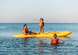 A family enjoys the Kayak Rental in Salou and jumps happily into the water together with Estació Nàutica Costa Daurada.