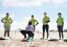 One of the surf instructors from Wanted Surf School Carcavelos is showing a group of friends how to surf during their surfing lessons near Lisbon.