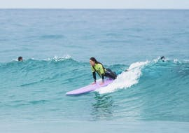 A young woman is confidently riding a wave during her Private Surfing Lessons near Lisbon with Wanted Surf School Carcavelos.