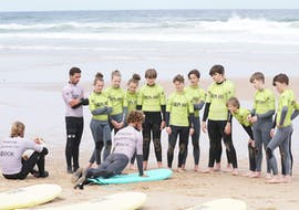 A group of kids is watching their surf instructor from Wanted Surf School Carcavelos demonstrate how to stand up on a surf board during their surfing lessons near Lissabon.