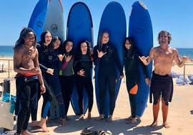 A group of young women and their surf instructros from Lisbon Surfaris are smiling at the camera as they get ready for their surfing lessons on Carcavelos Beach near Lisbon.