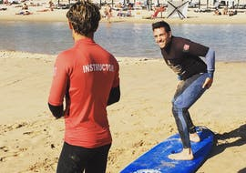 A young man is practicing the right surfing technique under the watchful eye of his surf instructor from Lisbon Surfaris during one of the private surfing lessons on Carcavelos Beach near Lisbon.
