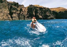 Two participants of the Mini Jet Ski Safari from Kamari Beach with Snorkeling organized by Kamari Beach Watersports Santorini are discovering the beautiful volcanic landscape of Santorini on a Jet Ski.
