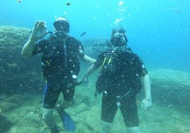 Two divers enjoy the beautiful view in the crystal clear sea during the Discover Scuba Diving in Jávea for Beginners with Four Divers Jávea.