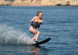 A girl riding her waterboard during Waterskiing at Armação de Pêra Beach with Moments Watersports.