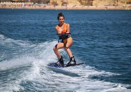 A girl riding her wakeboard during Wakeboarding at Armação de Pêra Beach with Moments Watersports.