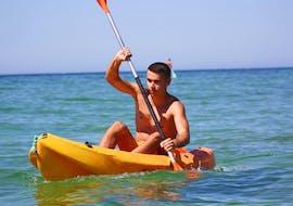 A young man is exploring the beautiful Algarve coast during his sea kayak rental at Praia de Armação de Pêra from Moments Watersports Algarve.