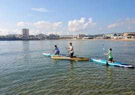 A father paddles with his two children comfortably across the sea during their Stand Up Paddling Lessons for Beginners at Beaches of Jávea with Siesta Advisor Jávea.