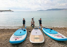 A father prepares together with his children on the beach for his tour, thanks to the SUP rental in Jávea from Siesta Advisor Jávea.