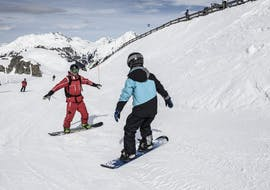 A group of snowboarders pose in the snow and look forward to their Snowboarding Lessons for Kids & Adults for Beginners with the Ski School St.Gallenkirch.