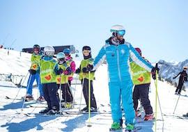 Un moniteur de ski de l'école de ski ESI Ski Family à Risoul montre aux enfants de son groupe les bons gestes avant de commencer leurs Cours de ski Enfants (5-13 ans) - Matin.