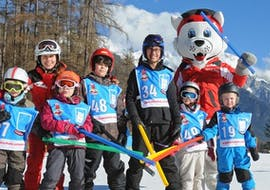 """A group of young children can be seen using colourful tools to help them learn to ski during their Kids Ski Lessons """"Bambini"""" (3-5 y.) with Skischule Schaber in Grünberg Obsteig."""