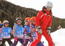A group of youngsters is lined up behind their ski instructor from Skischule Schaber in Grünberg Obsteig as they ski down the slope during their Kids Ski Lessons (5-16 y.) for Beginners.