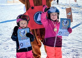 Two young girls receive their medal and certificate from mascot Foxy after they completed their Kids Ski Lessons (from 4 y.) for All Levels with Skischule Tannberg Lech.