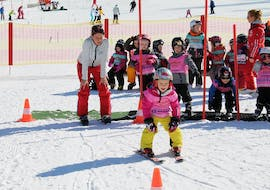 A child has a lot of fun with their ski school group and their ski instructor during the kids ski lessons (3 y.) with Skischule Brunner in Bad Kleinkirchheim.