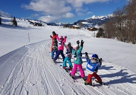 A group of kids is having fun while following their ski instructor on the slope during their Kids Ski Lessons (4-15 y.) for All Levels with Swiss Ski School Wildhaus.