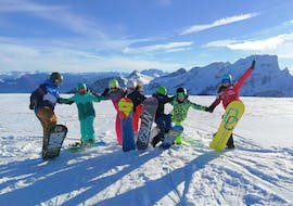 A group of children is taking a picture with their instructor during their Kids Snowboarding Lessons (8-15 y.) for All Levels with the Swiss Ski School Wildhaus.