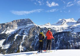 During the Private Ski Lessons for Adults of All Levels with Swiss Ski School Wildhaus, two participants are admiring the view over the mountains of Toggenburg.