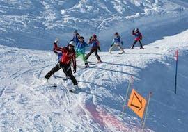 Un groupe d'enfants suit leur moniteur de ski de la Schweizer Skischule Zweisimmen sur la piste pendant leurs Cours de ski Enfants (3-16 ans) avec Expérience.