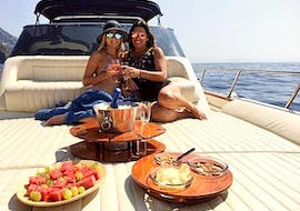 Two friends are enjoying a delicious mediterranean breakfast on the boat during the Boat Tour around Sorrento at Sunrise with Sunrise Sorrento.