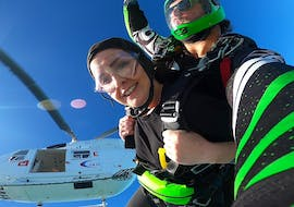 On the unique Helicopter Skydive near Christchurch with Skydiving Kiwis, a young lady is enjoying her freefall as she jumps out of a helicopter with her experienced tandem master.