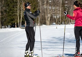 An instructor from Schweizer Skischule Grindelwald is showing a woman how to use her cross-country gear during the Introductory Cross-Country Skating Lessons for First Timers.