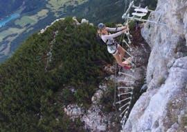 A brave participant is climbing up the Via Ferrata delle Aquile Paganella with LOLGarda.