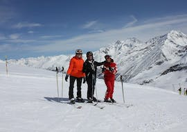 The ski instructor of Schweizer Skischule Saas-Fee is smiling for a picture with his customers during the private ski lessons for adults in the Valais.