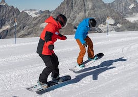 The snowboarding instructor of Schweizer Skischule Saas-Fee shows new tricks on the board to one of his customers during the private snowboarding lessons for kids and adults in the Valais.
