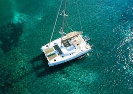 Spiridakos Sailing Cruises' Catamaran is floating on the crystal clear waters during the sailing catamaran cruise around the hotspots of Santorini.