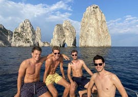 Four boys posing in front of the Faraglioni during the classic boat trip from Sorrento to Capri with Lubrense Boats Amalfi Coast.